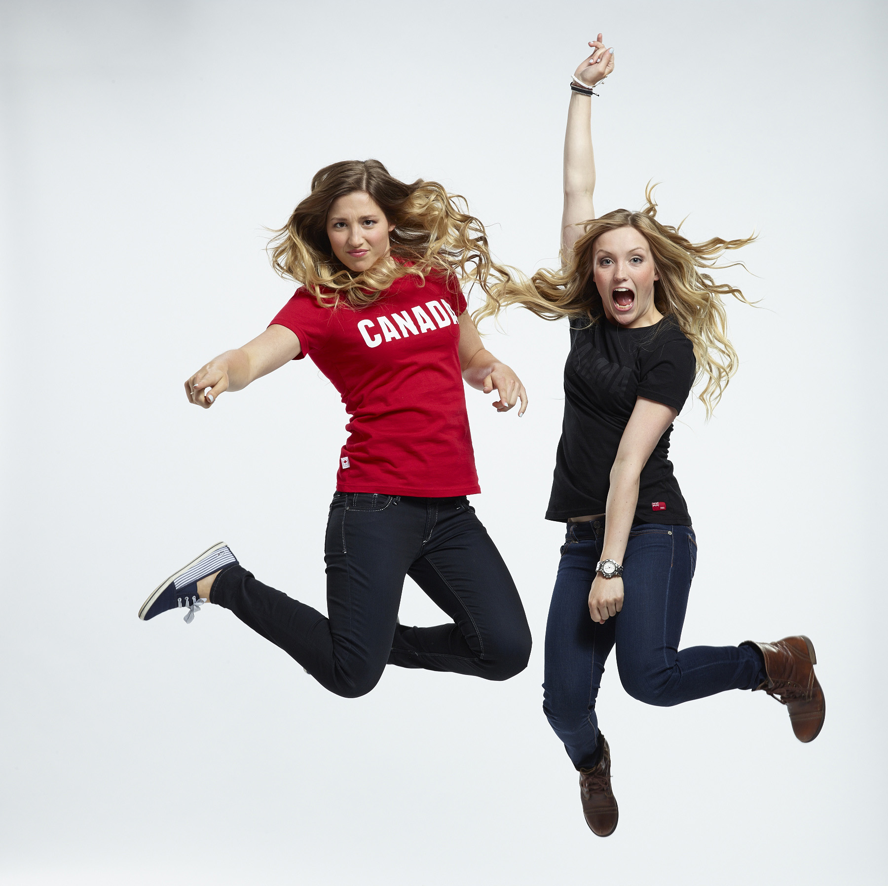 Two smiling female olympians jumping